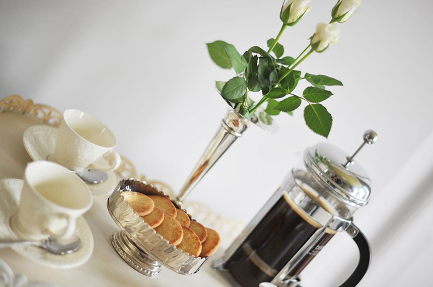 Fresh coffee with biscuits and flowers